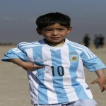 Five year-old Murtaza Ahmadi, an Afghan Lionel Messi fan, wears a shirt signed by Barcelona star Lionel Messi, as he plays football at the open area in Kabul, Afghanistan February 26, 2016.  REUTERS/Omar Sobhani